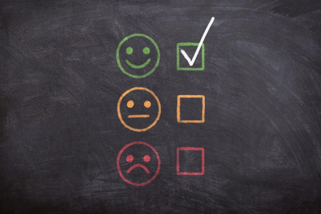 A imagem mostra um quadro negro com uma cara feliz, uma cara indiferente e uma cara triste. A cara feliz está assinalada.